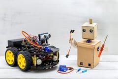 Två robotar är på tabellen, robotar, skruvmejslar, trådar, servo Royaltyfria Bilder