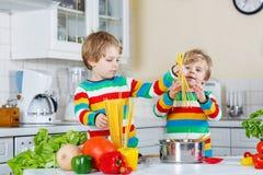 Två roliga barn som lagar mat italienskt mål med spahetti Arkivfoto