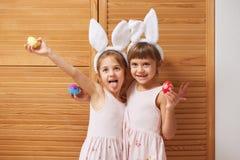 Två roliga charmiga lilla systrar i klänningarna med vita kanins öron på deras huvud rymmer färgade ägg i deras händer royaltyfri bild