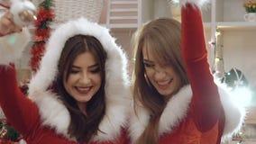 Två roliga damer som dansar och att le med julleksaker stock video