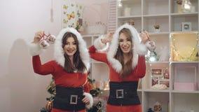 Två roliga damer som dansar och att le med julleksaker i 4K stock video
