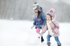 Två roliga förtjusande lilla systrar i vinter parkerar Royaltyfria Bilder