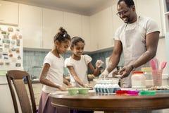 Två roliga flickor som lagar mat pajen med deras älska hjälpsamma fader fotografering för bildbyråer