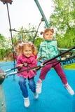 Två roliga flickor tillsammans på raster av lekplatsen Royaltyfri Bild
