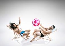 Två roliga grabbar som sitter på deckchairs Royaltyfri Fotografi