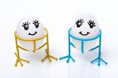 Två roliga le ägg på ställning på vit bakgrund arkivbild