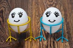 Två roliga le ägg på ställningar på en träbakgrund arkivbild