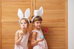 Två roliga lilla systrar i klänningarna med vita kanins öron på deras huvud har gyckel med färgade ägg i deras händer royaltyfri bild