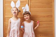 Två roliga lilla systrar i klänningarna med vita kanins öron på deras huvud har gyckel med färgade ägg i deras händer arkivbild