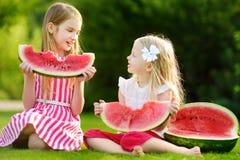 Två roliga lilla systrar som utomhus äter vattenmelon på varm och solig sommardag Arkivbilder