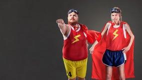 Två roliga män i dräkter av superheroes Gör tunnare och fett folk royaltyfria bilder
