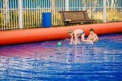 Två roliga pojkar spelar vattenfotboll i en uppblåsbar utomhus- pöl royaltyfria foton