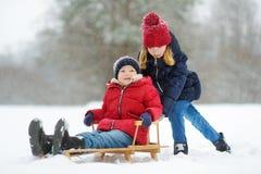 Två roliga små flickor som har gyckel med en släde i härlig vinter, parkerar Gulliga barn som spelar i en snö arkivfoto