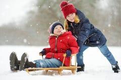 Två roliga små flickor som har gyckel med en släde i härlig vinter, parkerar Gulliga barn som spelar i en snö fotografering för bildbyråer