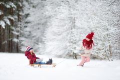 Två roliga små flickor som har gyckel med en sleight i härlig vinter, parkerar Gulliga barn som spelar i en snö Royaltyfria Bilder