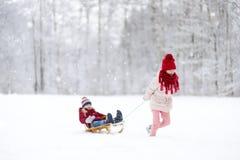 Två roliga små flickor som har gyckel med en sleight i härlig vinter, parkerar Gulliga barn som spelar i en snö Arkivfoton