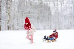 Två roliga små flickor som har gyckel med en sleight i härlig vinter, parkerar Gulliga barn som spelar i en snö Arkivfoto