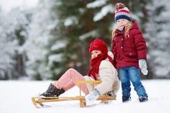 Två roliga små flickor som har gyckel med en sleight i härlig vinter, parkerar Gulliga barn som spelar i en snö Royaltyfri Fotografi