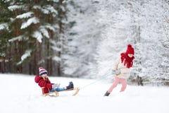 Två roliga små flickor som har gyckel med en sleight i härlig vinter, parkerar Gulliga barn som spelar i en snö Royaltyfri Foto