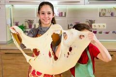 Två roliga ungar med tunn deg täcker och att göra pizza Royaltyfri Fotografi
