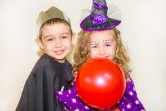 Två roliga ungar som bär häxa- och vampyrdräkten på halloween Arkivbild