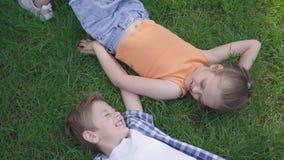 Två roliga ungar som ligger på gräset i, parkerar att le till varandra Flickan som tar handen av pojken Ett par av lyckligt lager videofilmer