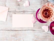 Två rosa champagneexponeringsglas med det tomma pappers- kortet Arkivfoto