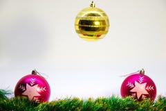 Två rosa färger, en guld på de bästa julbollarna och julgarnering på en vit bakgrund Royaltyfri Fotografi