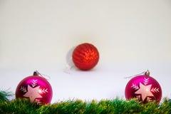 Två rosa festliga bollar med en röd boll i mitt och julgarnering på en vit bakgrund Royaltyfri Bild