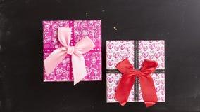 Två rosa gåvaaskar på den lekmanna- lägenheten för bakgrund för kritabräde Arkivfoton