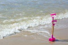 Två rosa skyfflar i sanden Arkivfoton