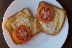 Två rostade bröd med ägg och tomaten royaltyfria bilder