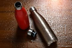 Två rostfria thermo flaskor på en trätabell som besprutas med vatten Med solljuseffekt arkivbilder