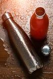 Två rostfria thermo flaskor på en trätabell som besprutas med vatten Med solljuseffekt royaltyfria bilder
