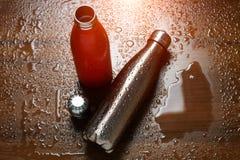 Två rostfria thermo flaskor på en trätabell som besprutas med vatten Med solljuseffekt arkivfoton