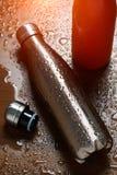 Två rostfria thermo flaskor på en trätabell som besprutas med vatten Med solljuseffekt fotografering för bildbyråer