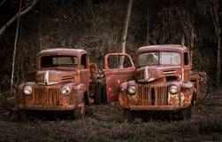 Två rostiga gamla Ford lastbilar Arkivfoto