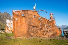 Två rostiga gamla valfångare som sättas på land bredvid skeppsdocka Arkivfoton