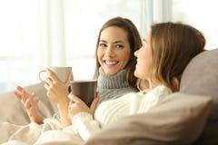 Två rumskamrater som talar på soffan i vinter royaltyfria bilder