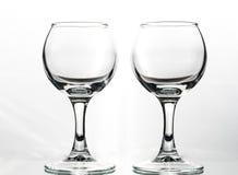 Två runda exponeringsglas tömmer eller fullt med vågor av flytande på en vit bakgrund arkivfoton