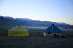 Två runda hus av turister på en bakgrund av berg Royaltyfria Bilder