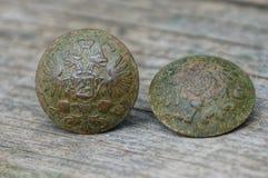 Två runda kopparknappar med ett emblem och en örn på en grå tabell royaltyfri foto