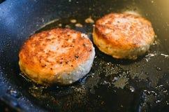 Två runda kotletter från kött av nötkött stekas i en stekpanna och en olja Arkivbild