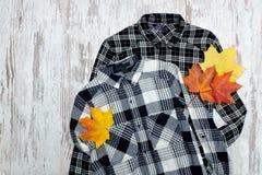Två rutiga skjortor och lönnlöv trendigt begrepp Arkivfoto