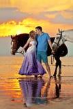 Två ryttare på hästrygg på solnedgången på stranden Vänritthors Arkivfoton