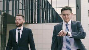 Två säkra affärsmän som är på deras väg till kontorsbyggnaden stock video