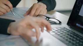 Två säkra affärsmän som samarbetar på projektet som inomhus sitter på tabellen med bärbara datorn arkivfilmer