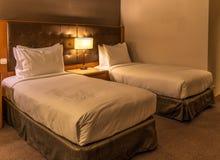 Två sängar och gemensamt nackstöd med tabelllampan i ett standart hotellrum royaltyfria foton