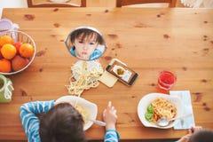 Två söta barn, pojkebröder och att ha för lunchspagetti på Arkivbild