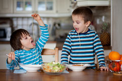 Två söta barn, pojkebröder och att ha för lunchspagetti på royaltyfri foto